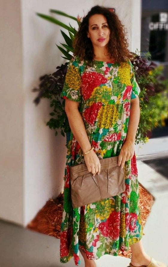 a reviewer wearing the dress with bright florals on it