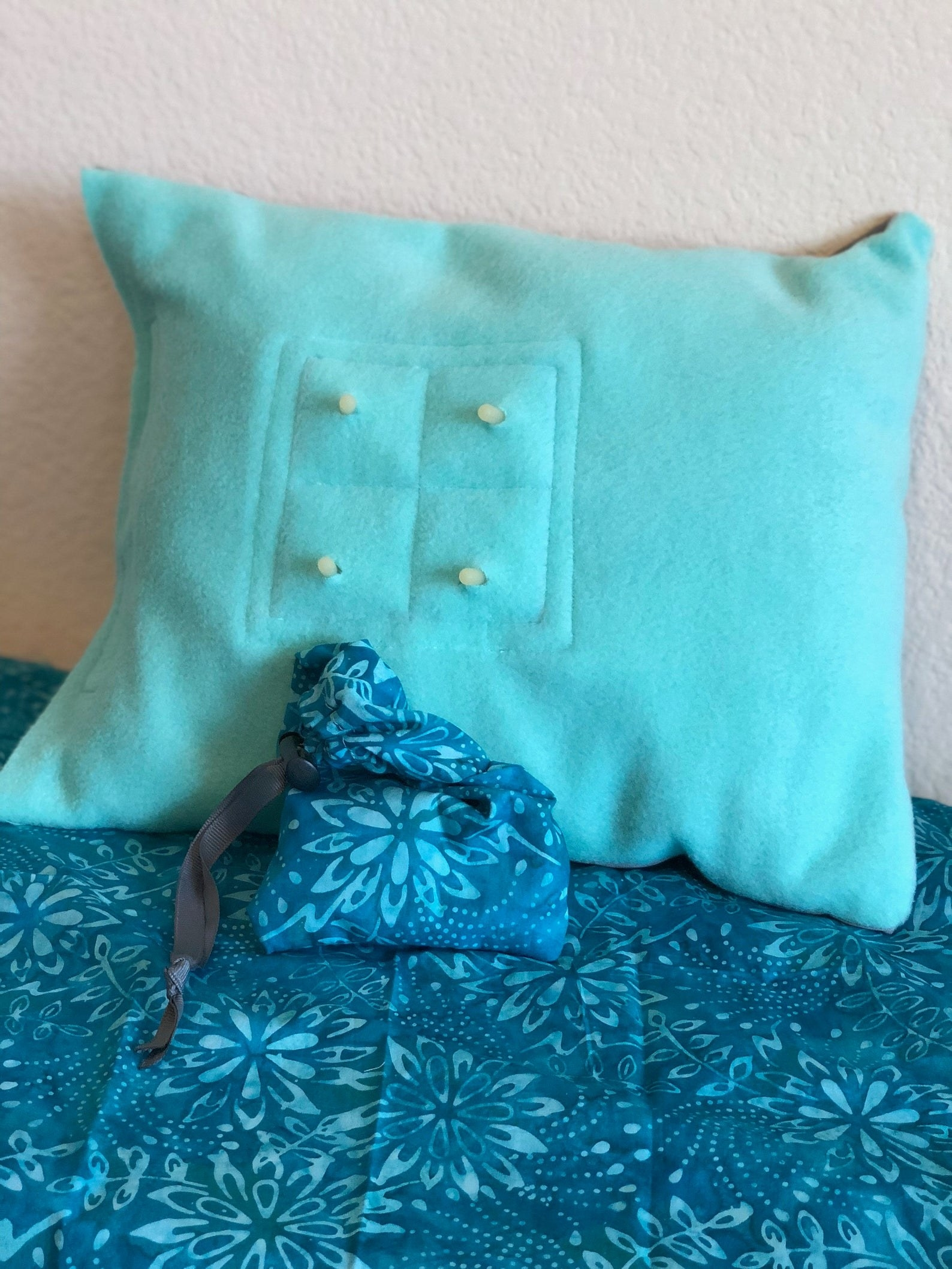 The pillow in the color teal