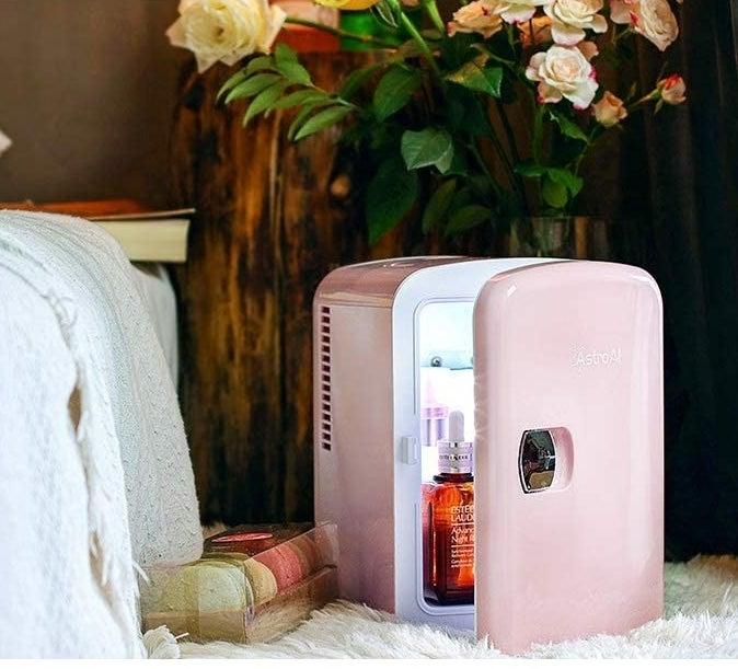 the mini fridge partially open next to a bed