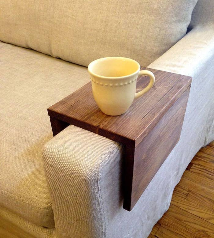 Wooden arm rest table installed on couch with coffee cup on top