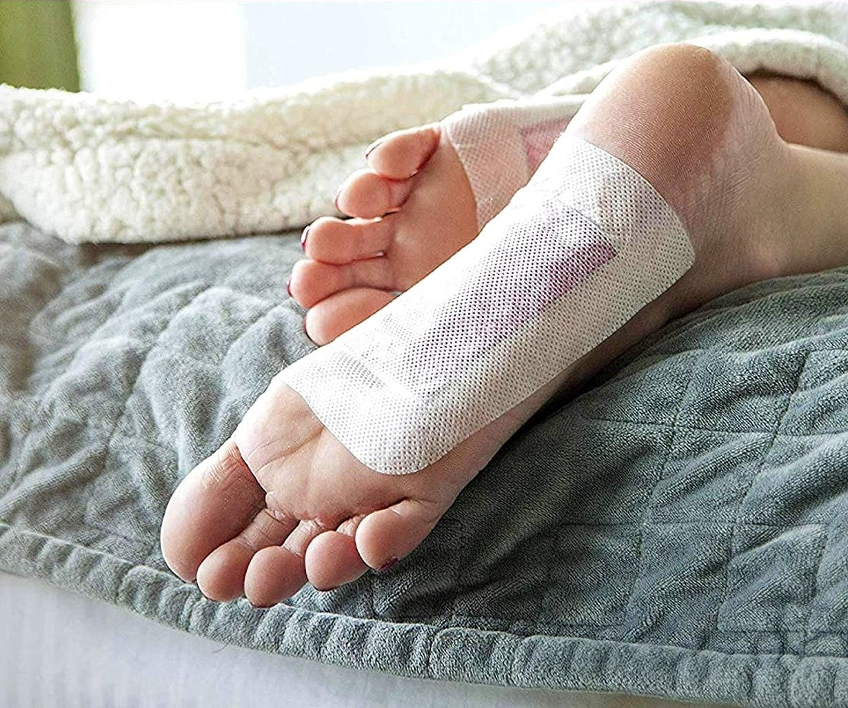 A close up of the bottom of a person's feet where the pads have been applied