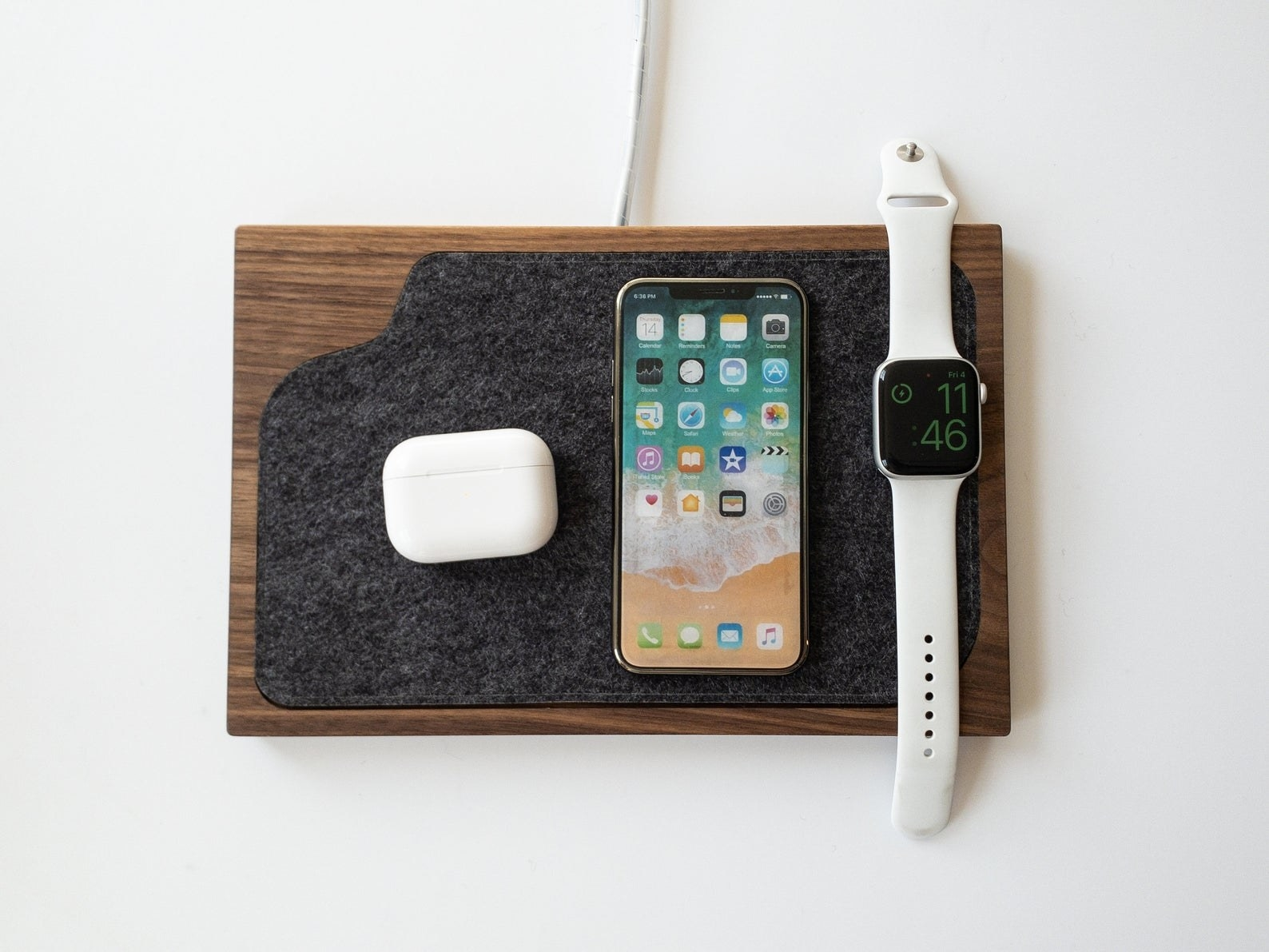 the wireless charging tray with a smart phone, watch, and airpods on it