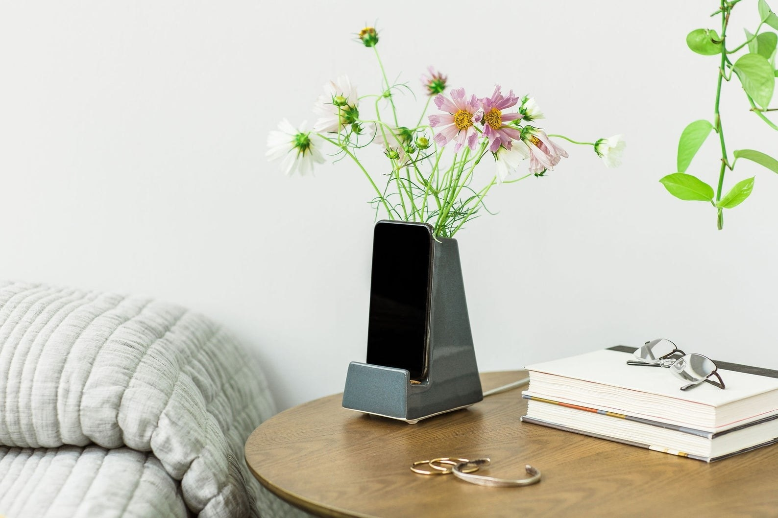 Phone holder vase placed on table with flower and phone placed inside
