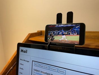 Smartphone placed in mount attached to laptop