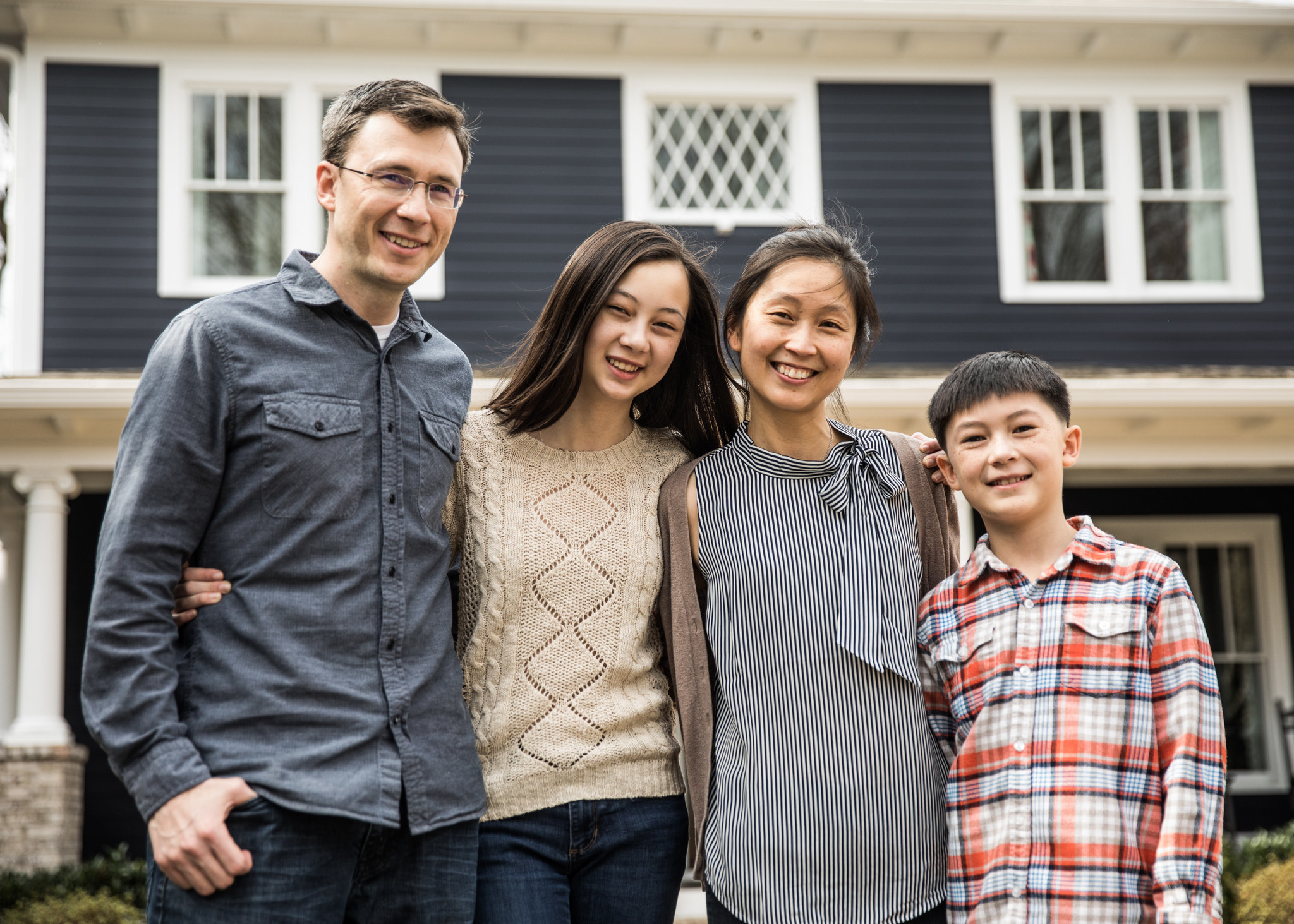 mixed race family smiling and posing together