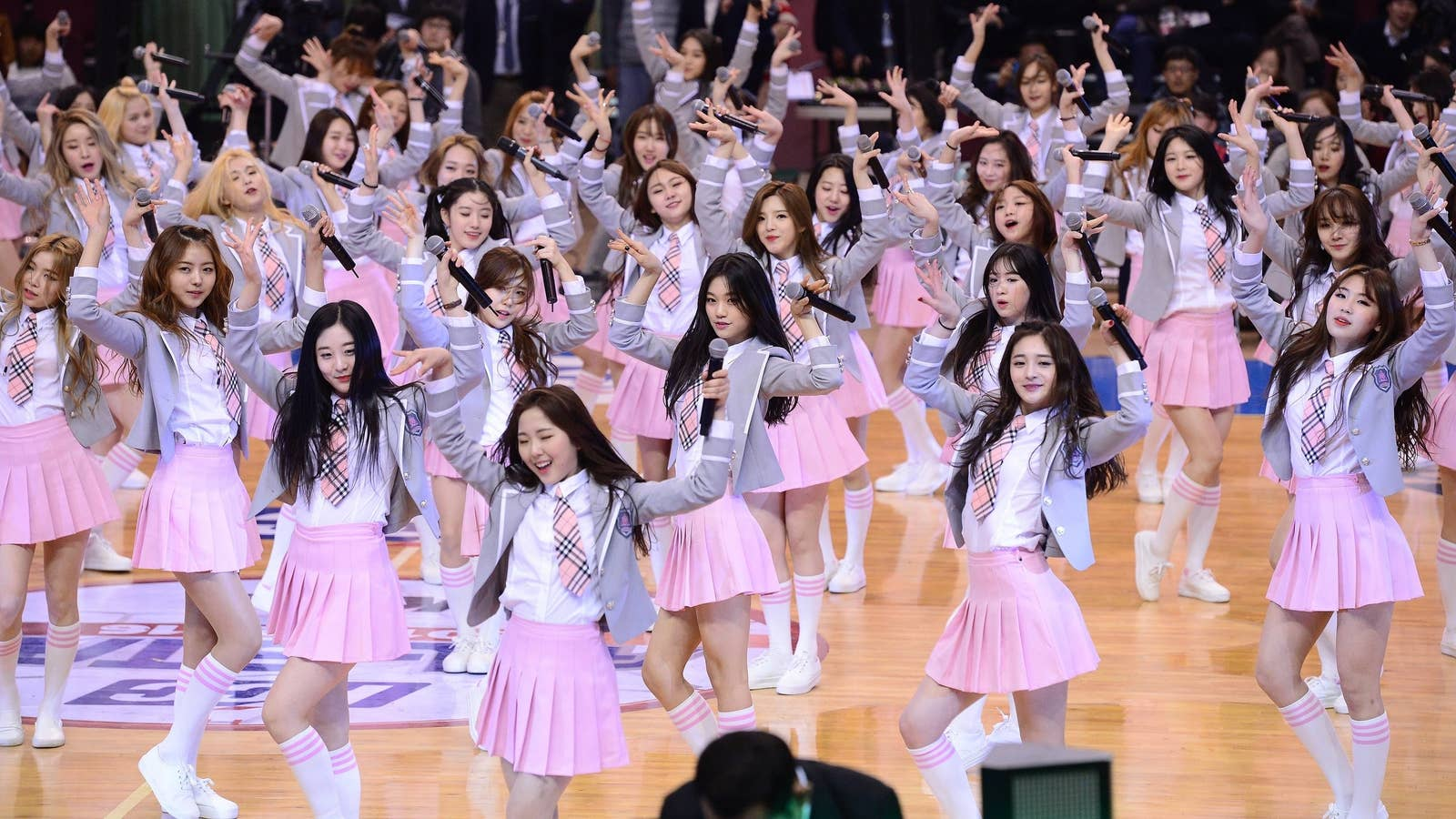 Dozens of K-pop girls wear skirts, ties, and blazers and pose for the camera while holding microphones