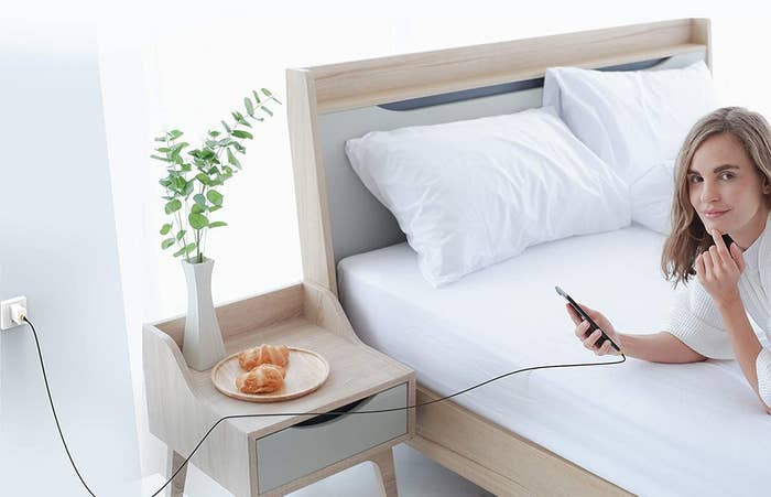 person lying on the bed with their phone lugged in via long charger