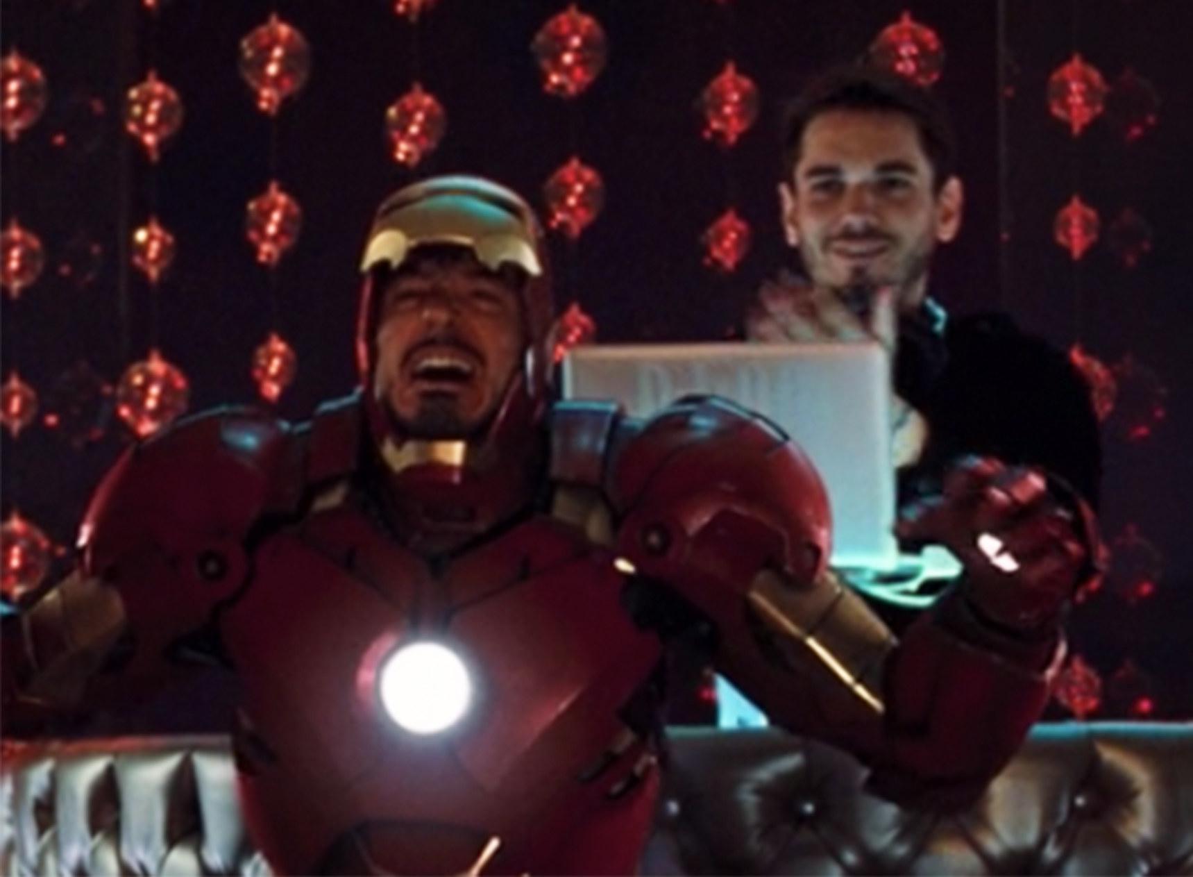DJ AM cheers behind Tony Stark