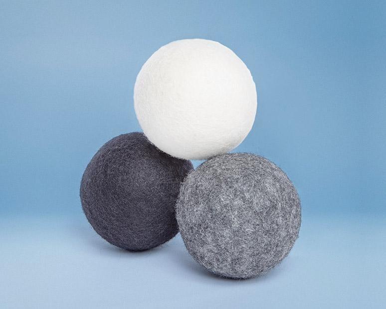 the three dryer balls in white, light gray, and dark gray