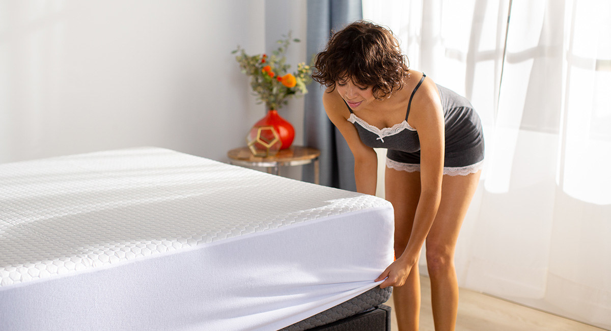 Model pulling a white mattress cover taut over a bed