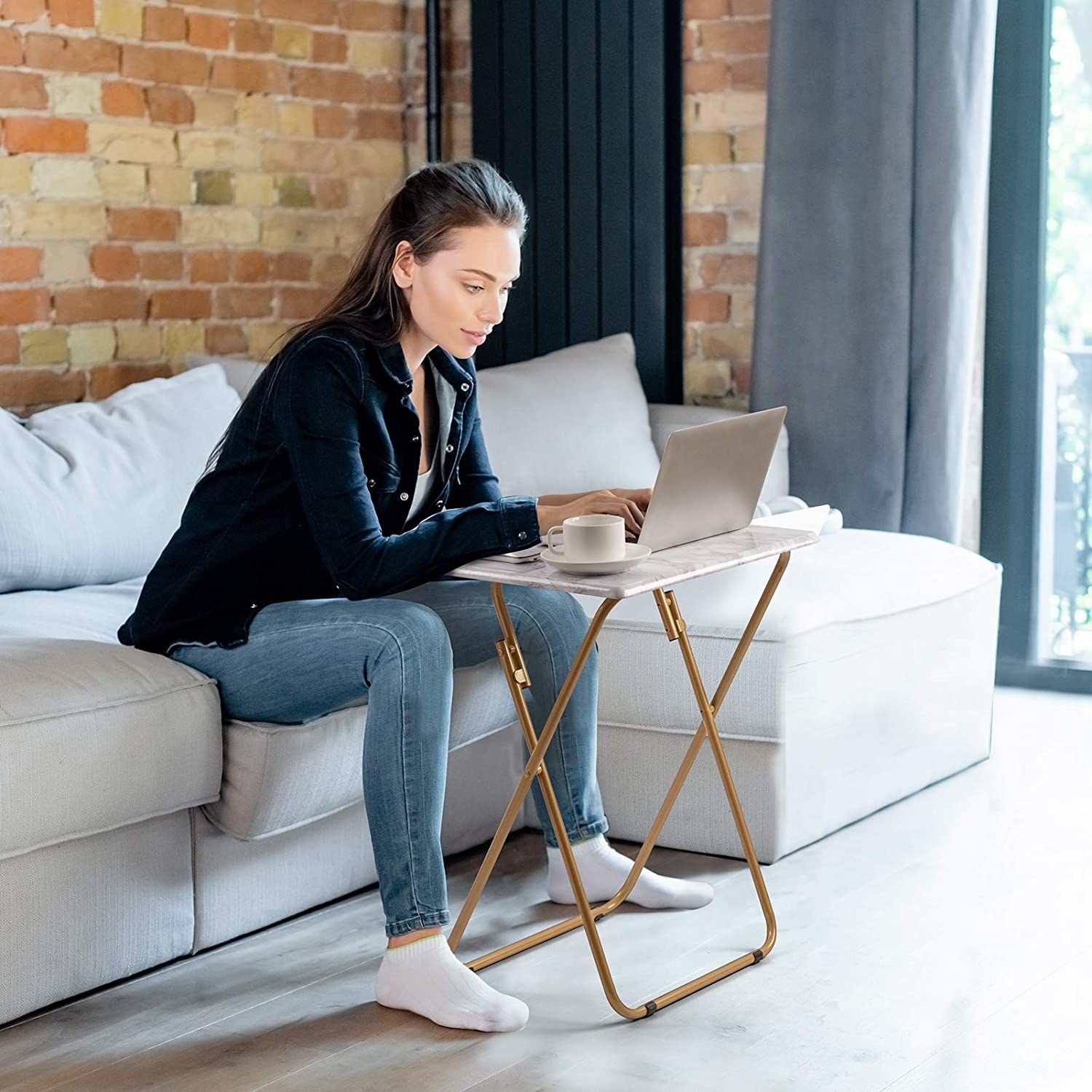 Model sitting on couch with folding table in front