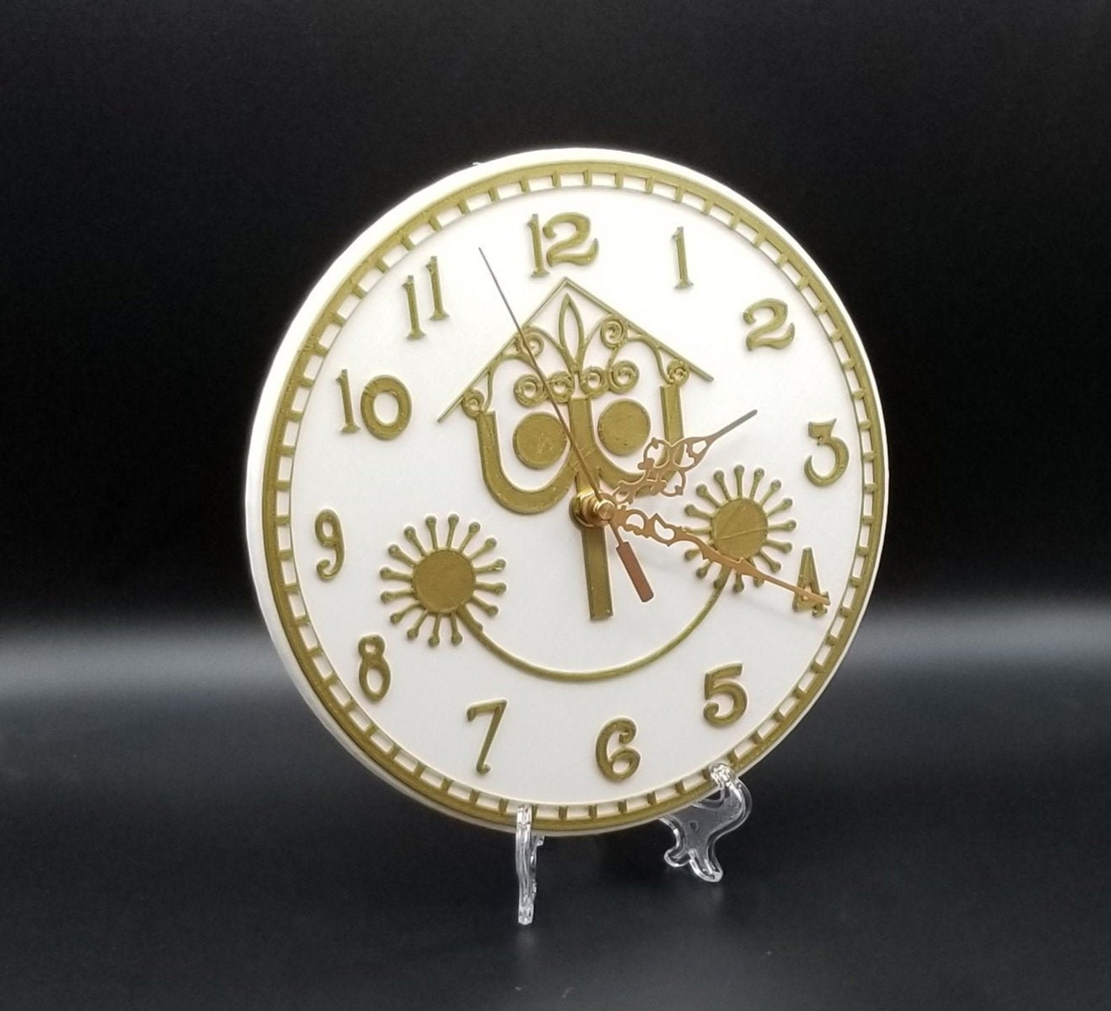 a white and gold clock that looks like the one from it's a small world