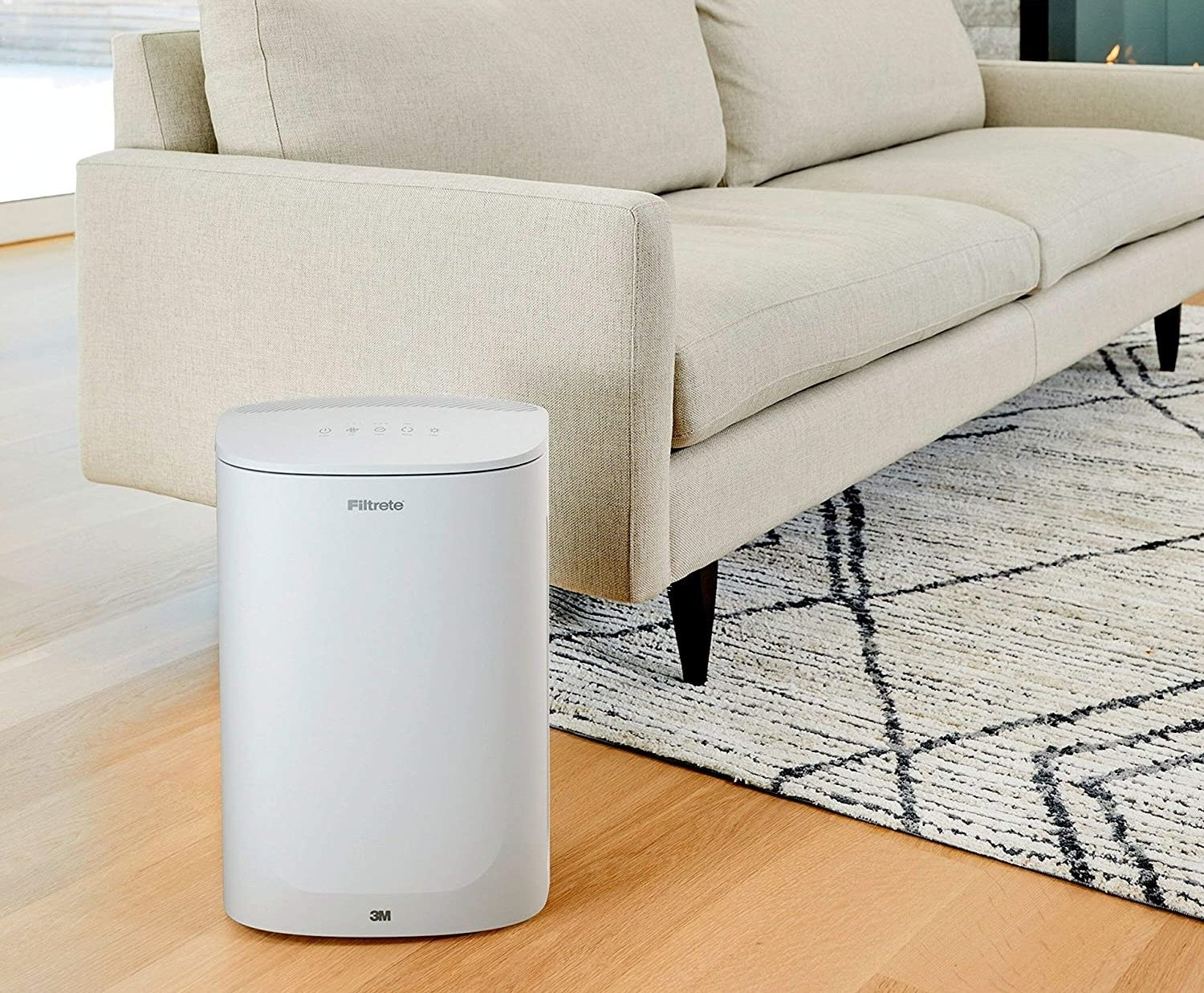 A white air purifier about the size of a of medium trash can next to a couch in a living room