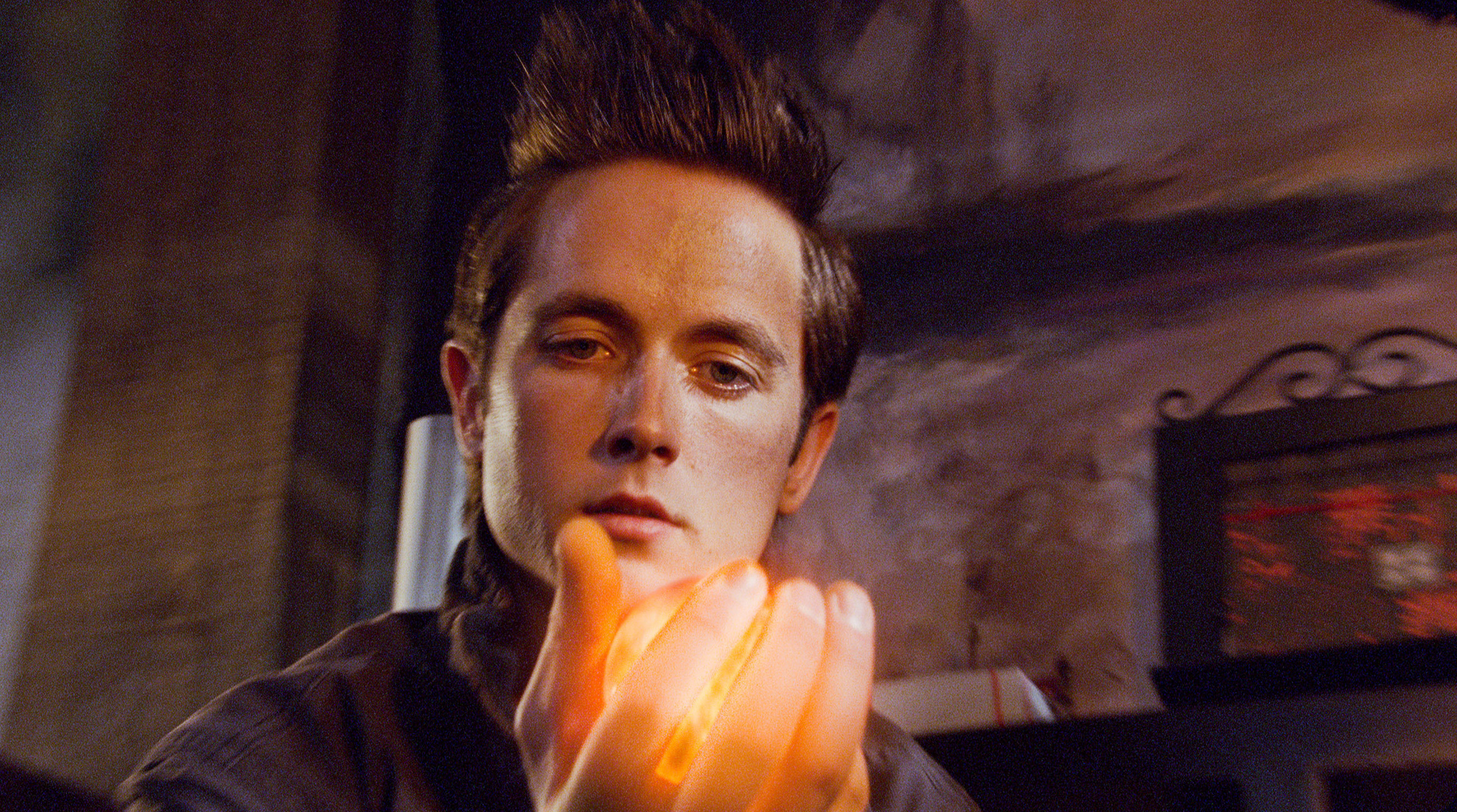 Justin Chatwin holds a glowing orb in his hand