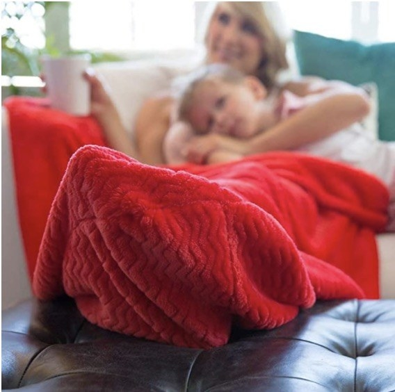model on couch with feet in red blanket's pocket