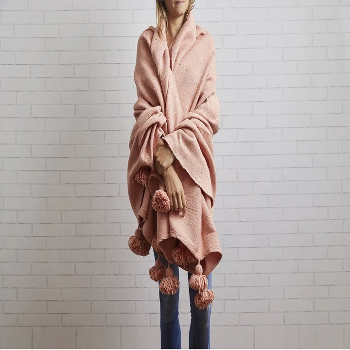 model wrapped in pink blanket with large tassels on the end