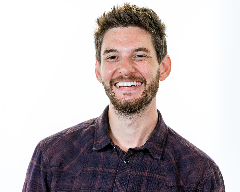 Ben Barnes smiling in a plaid shirt