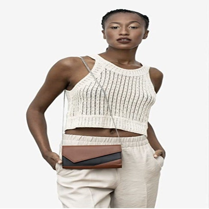model wearing the same hip-length bag, in brown with black accent