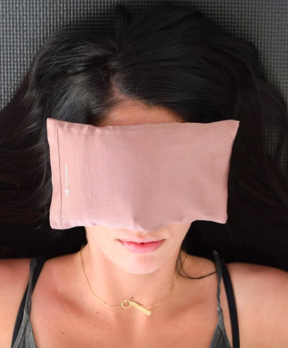 A person lying on a bed with the eye pillow over their face