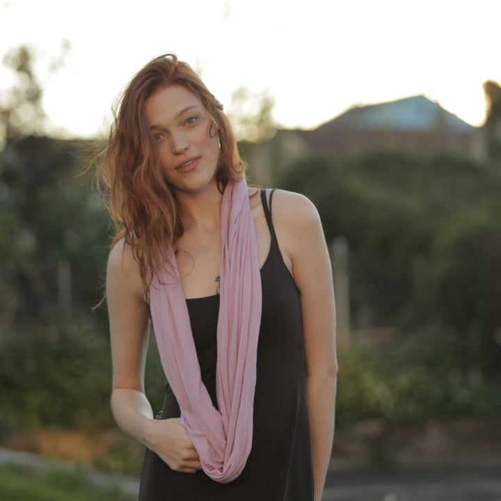 a model wears the scarf in pink