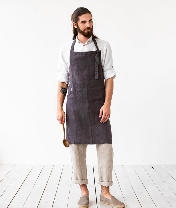 Person wearing apron over outfit also made with linen. The apron hits just above the knees and is tied at the neck.