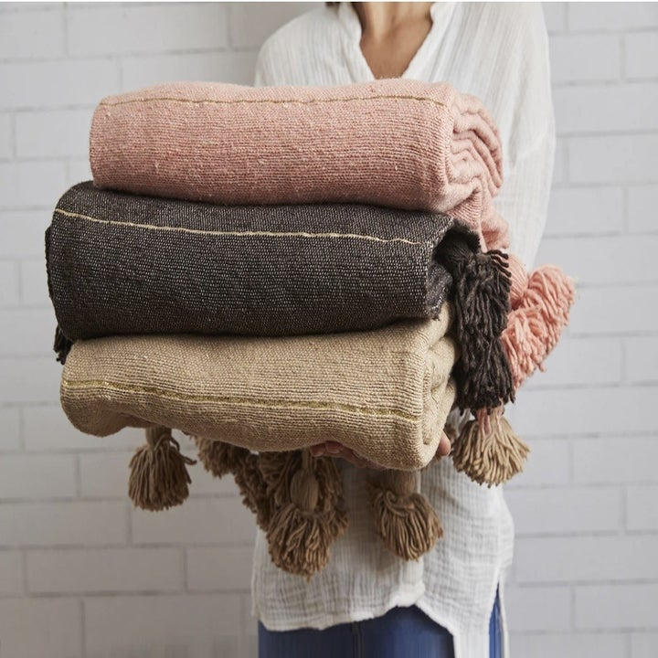 stack of the blankets in pink, dark grey, and taupe