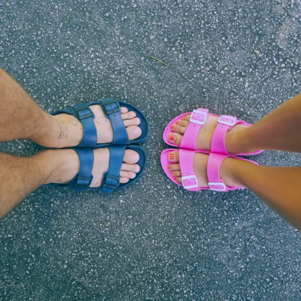 two reviewers's pairs of feet: one in the blue, the other in the pink Birkenstocks