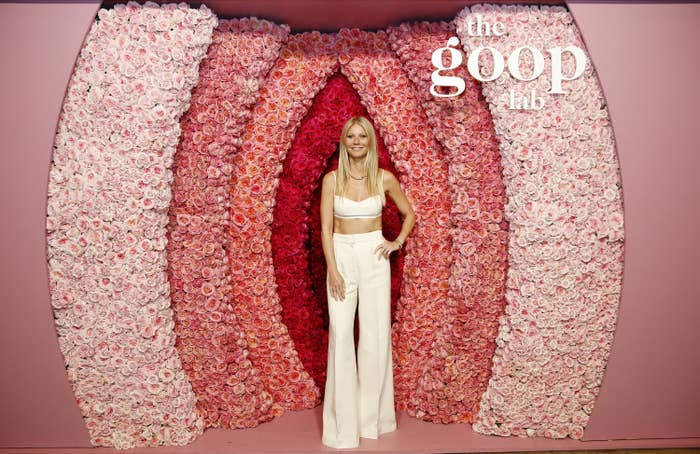 Gwyneth stands in front of a wall of pink flowers