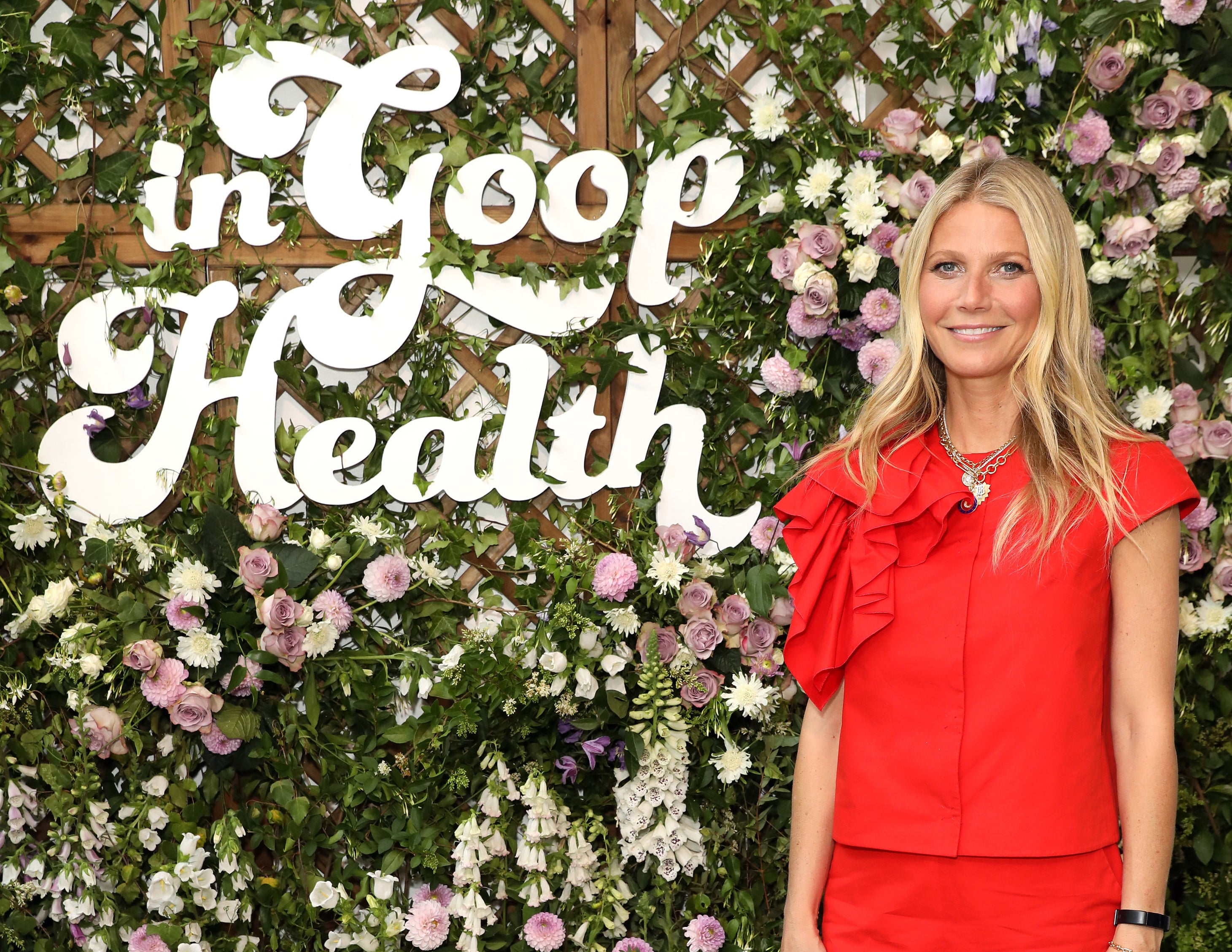 Gwyneth stands in front of a sign that says in goop health
