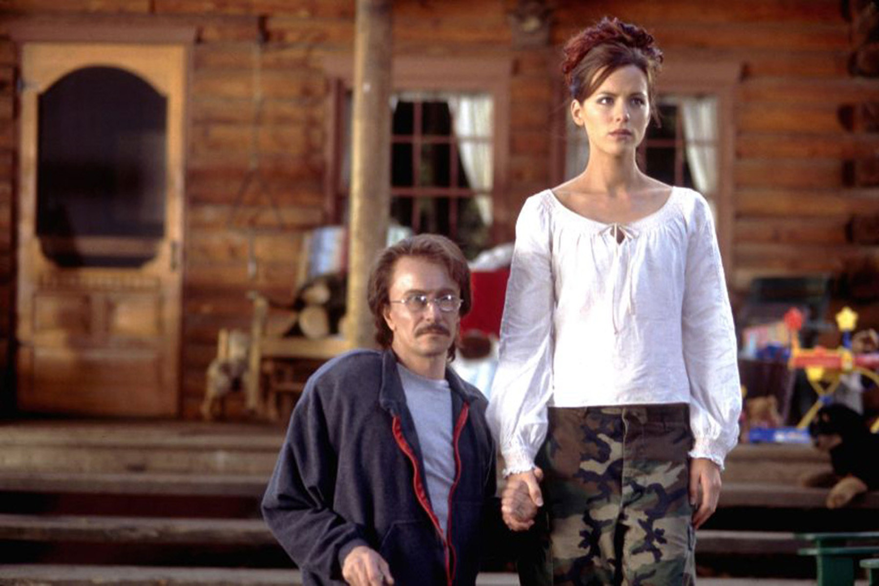 Gary Oldman holding hands with Kate Beckinsale in front of a house