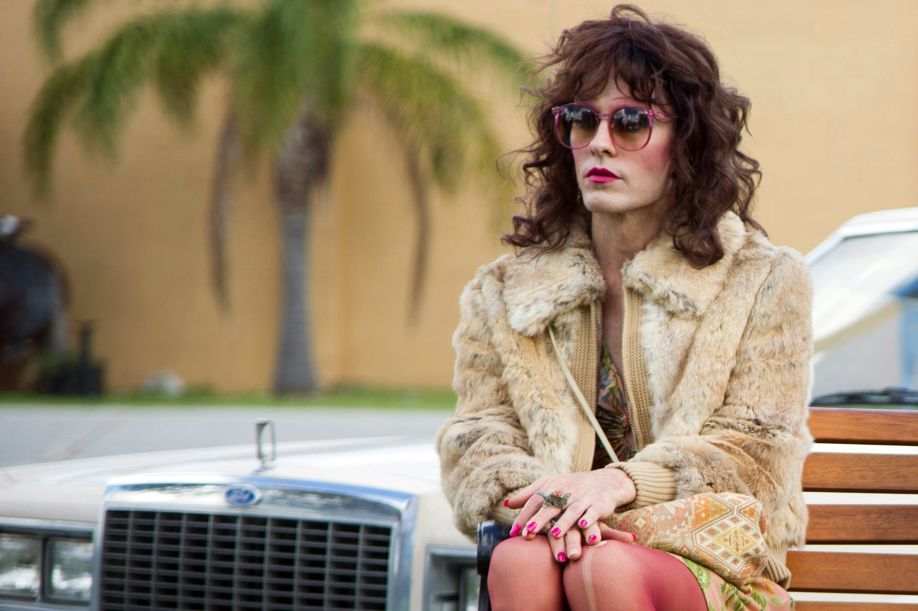 Jared Leto's character, Rayon, sits on a bench in front of a car