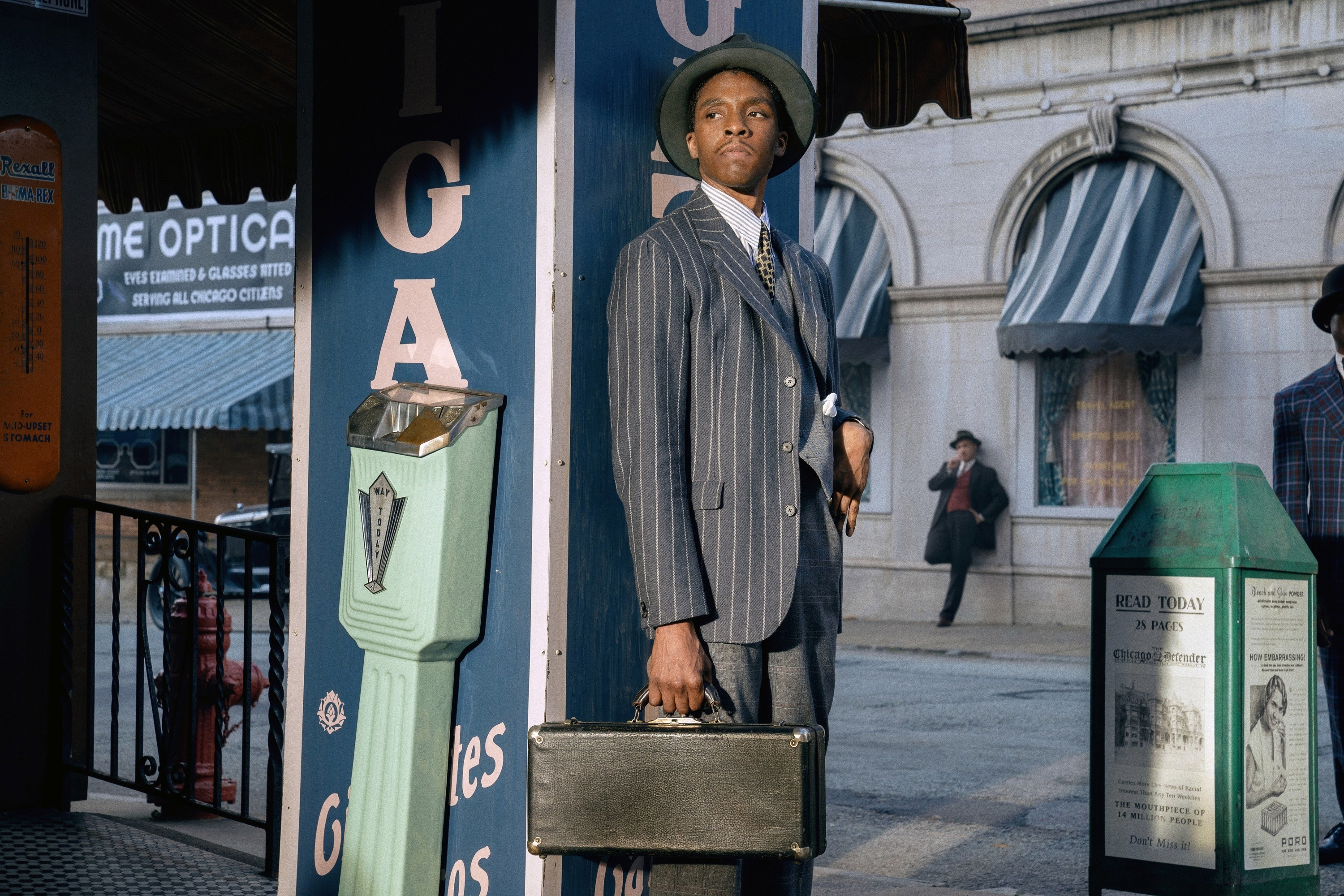Boseman stands carrying a suitcase in Ma Rainey's Black Bottom