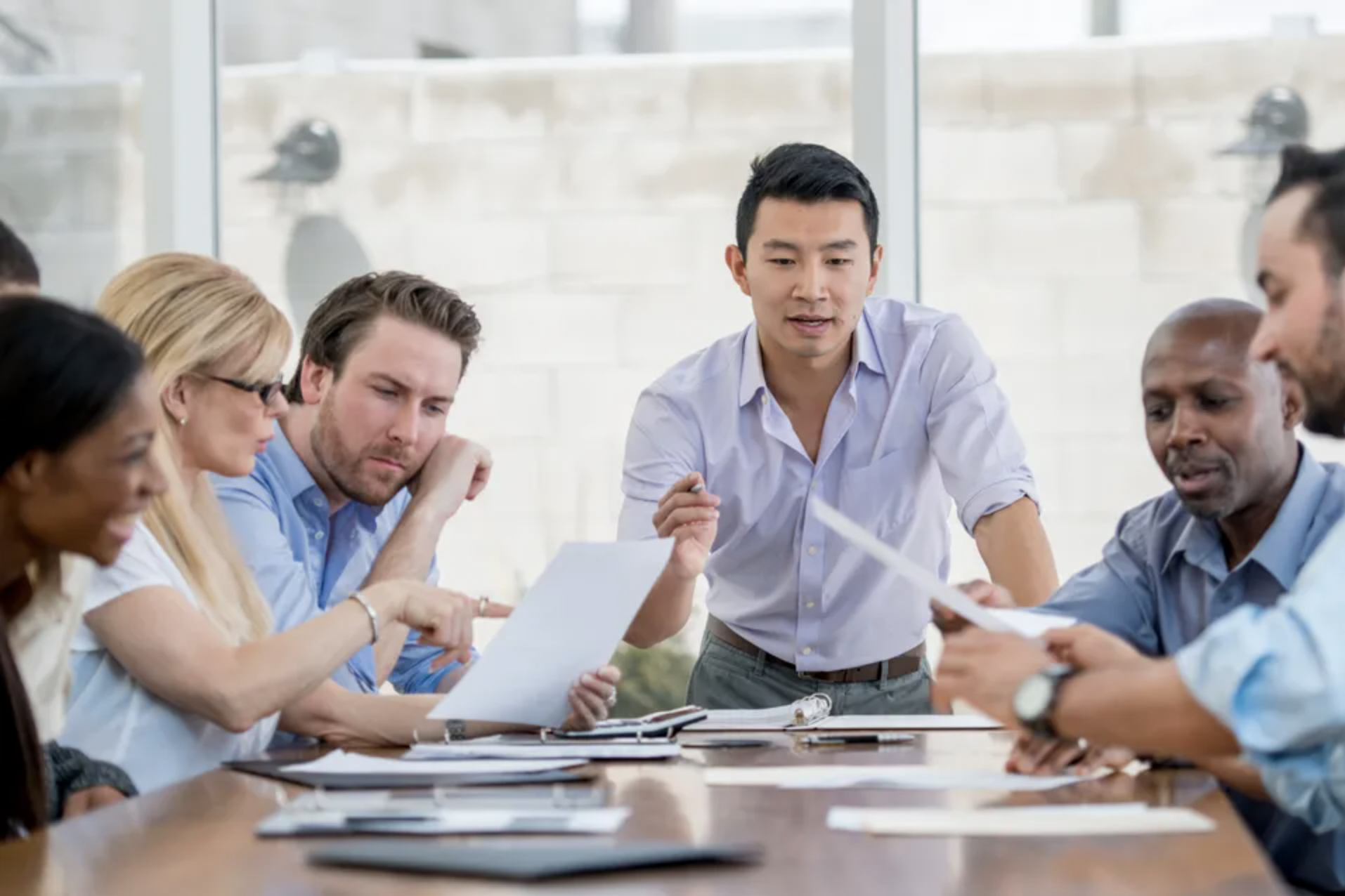 Stock photo of Simu Liu giving a boardroom presentation to a multi-ethnic group of business professionals.