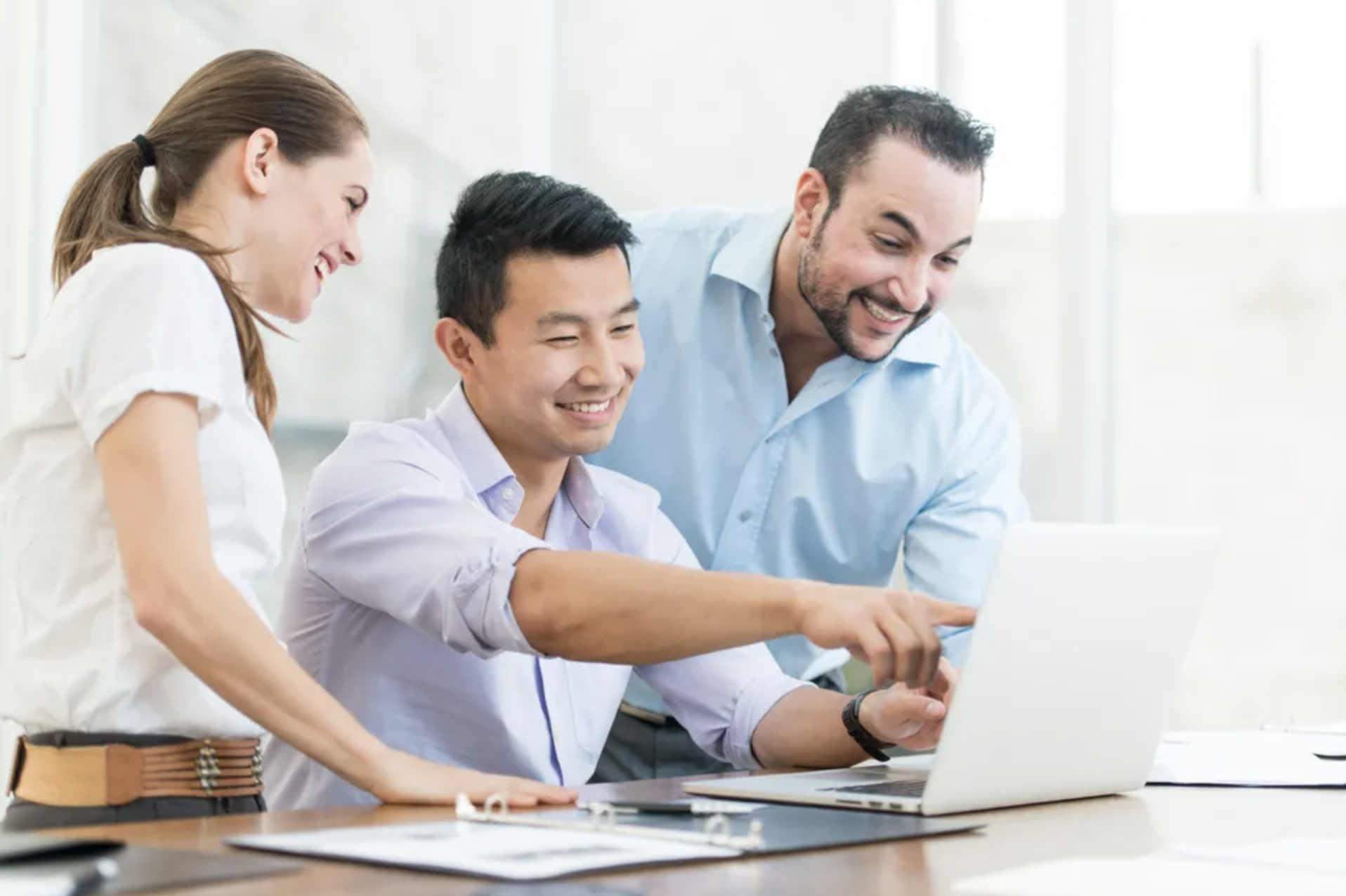 Stock photo of Simu Liu participating in internet research in the office; A multi-ethnic group of business professionals doing internet research and are surfing the web together in the office.