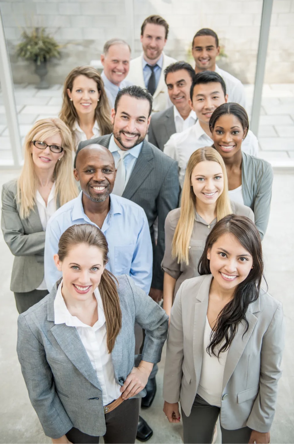 A multi-ethnic group of business professionals are standing together in a group and are smiling while looking at the camera. Simu Liu is in peeping out in the back.