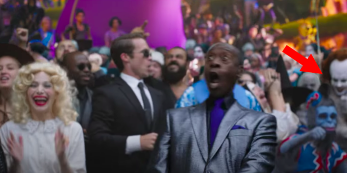 Pennywise in a crowd of people behind Don Cheadle
