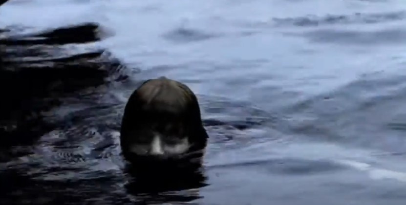 Pale boy peeking his head out of the water