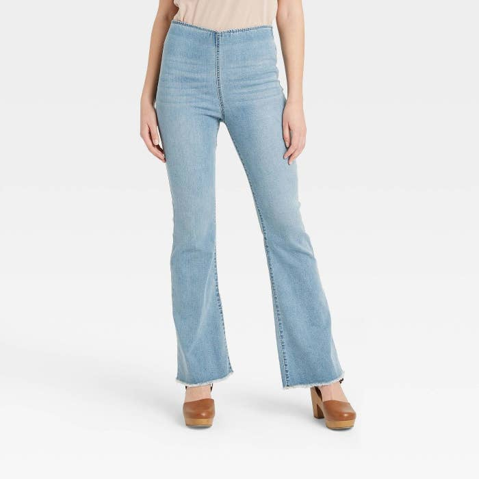 Model wearing slip-on light wash jeans with no buttons