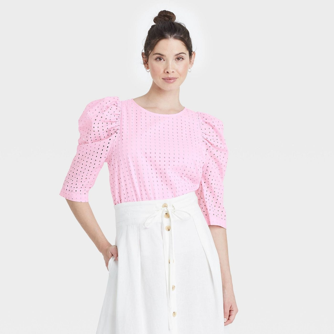 Model wearing pink top with 3/4 sleeves