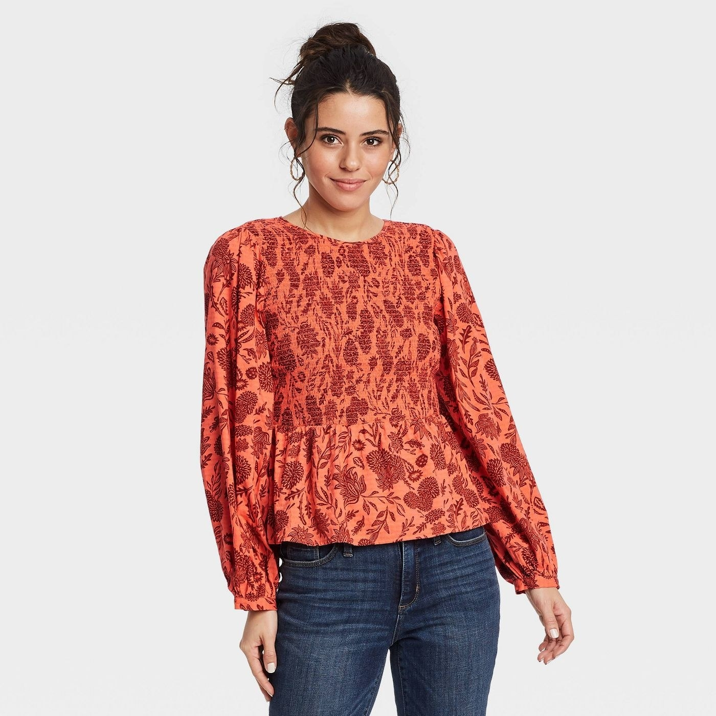 Model wearing orange top with a red floral pattern, stops at the waist