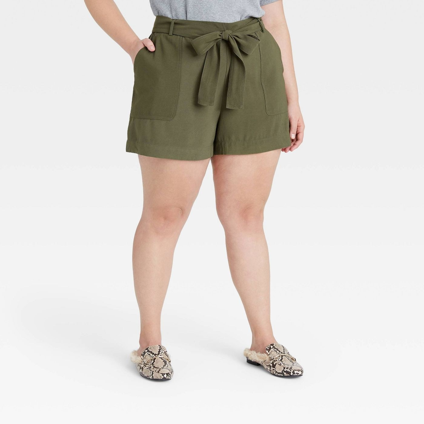 Model wearing green shorts with two pockets, shorts go past the thighs