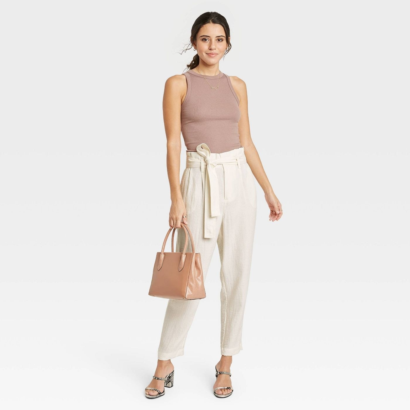 Model wearing off-white paper-bag pants with pockets and tie waist