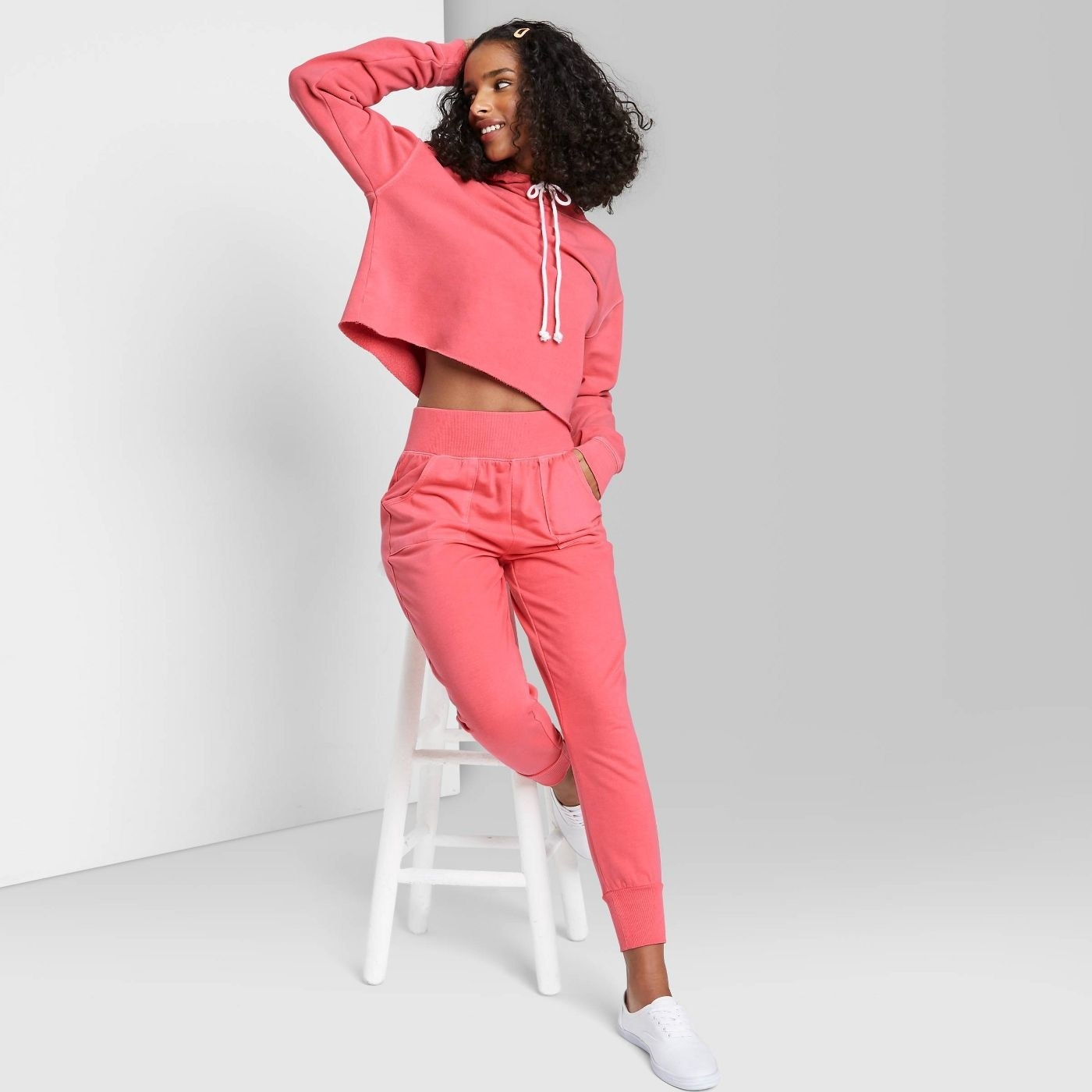 Model wearing coral joggers with thick waist band and pockets