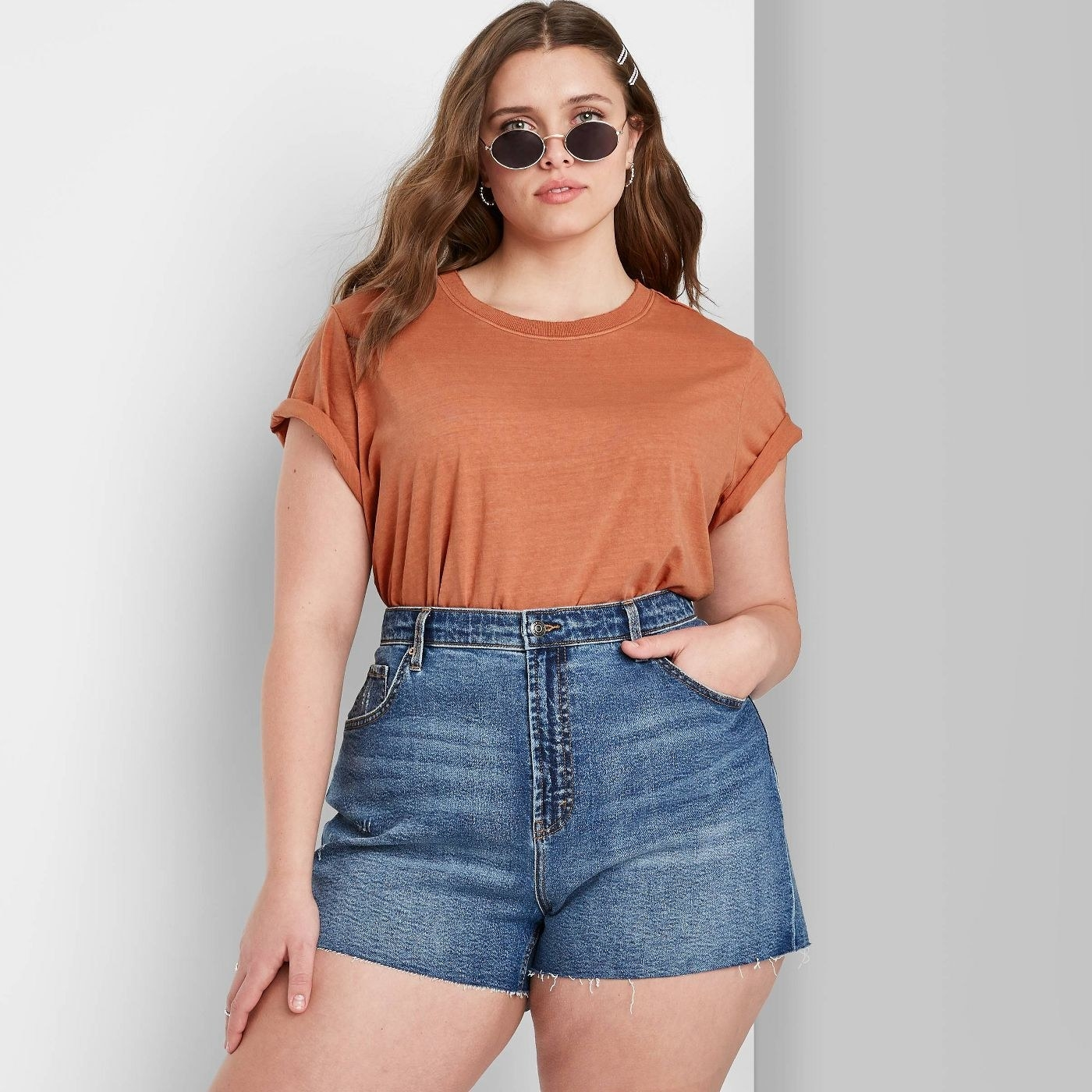 Model medium wash jean shorts that stop mid-thigh