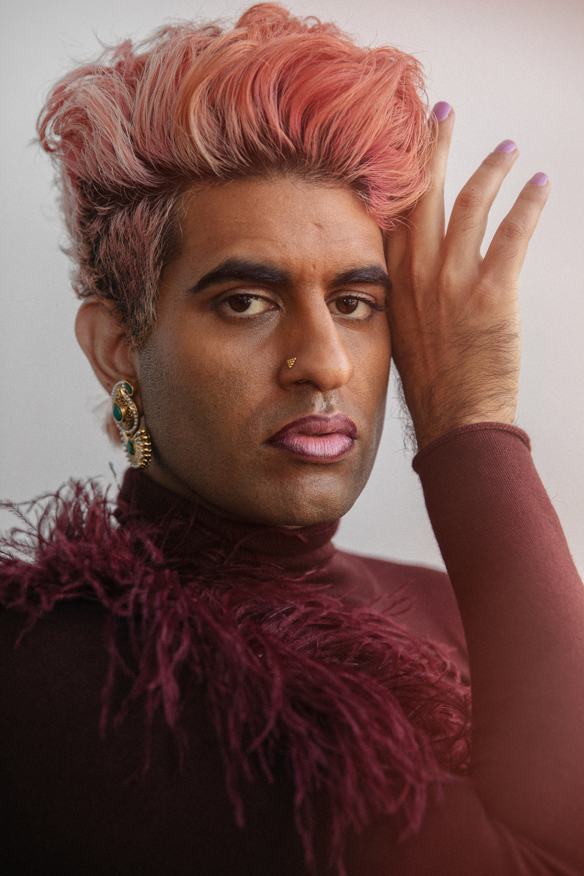 A closeup of a man with pink hair wearing a feather boa