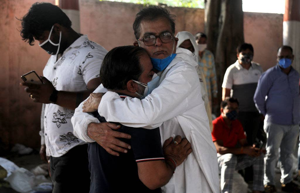 Two men embrace in India , wearing masks to protect from the coronavirus