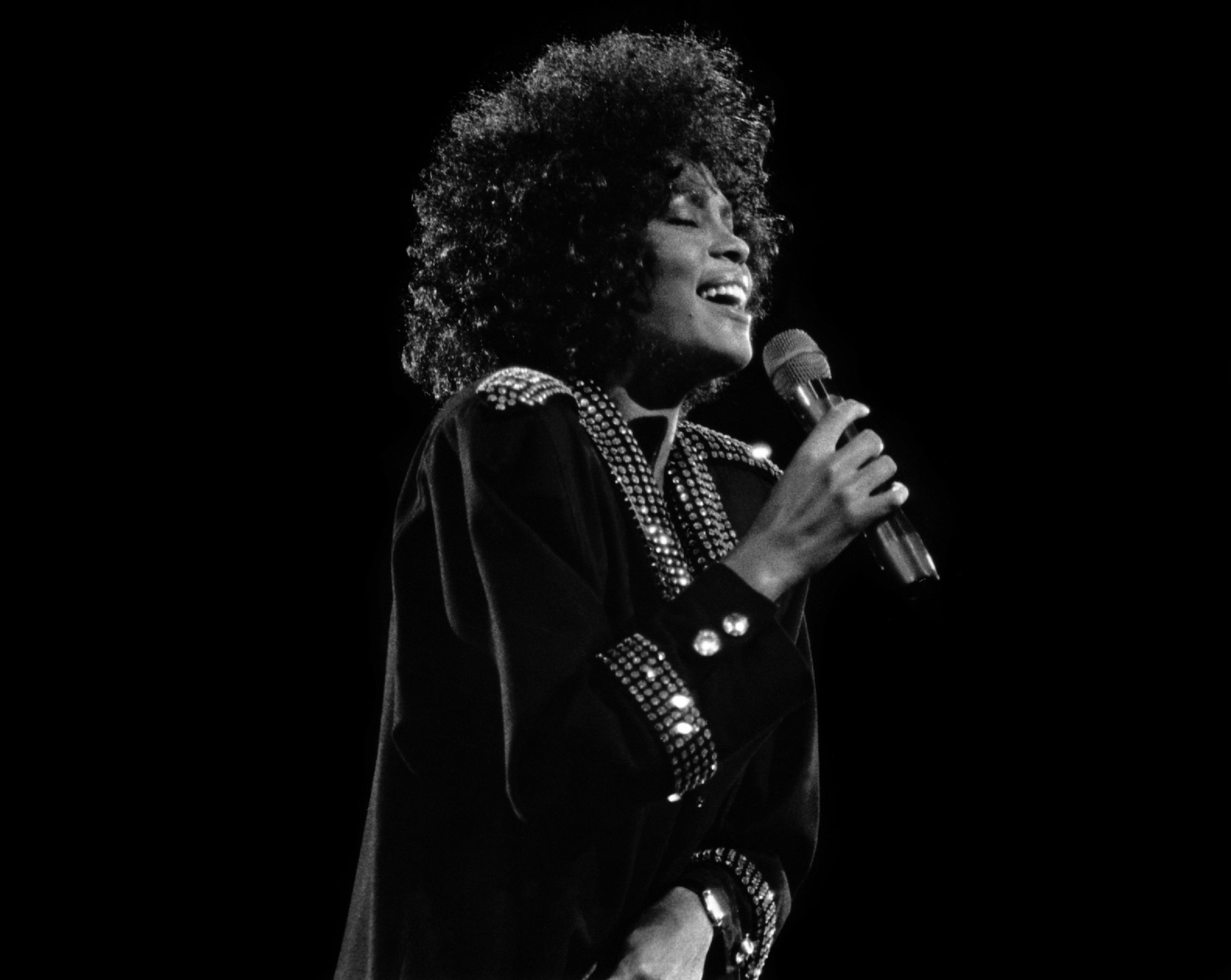 Whitney Houston with her eyes closed singling on stage