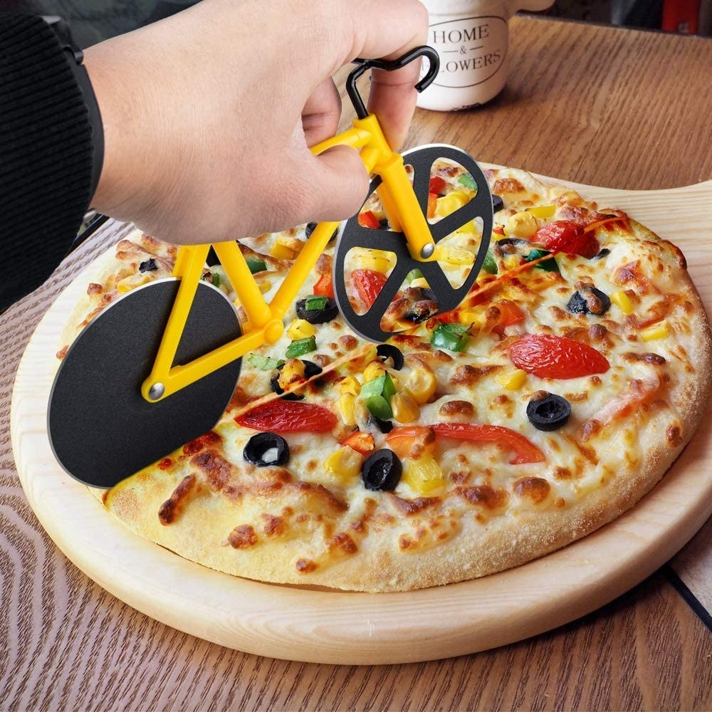 a bicycle-shaped pizza cutter slicing a pizza
