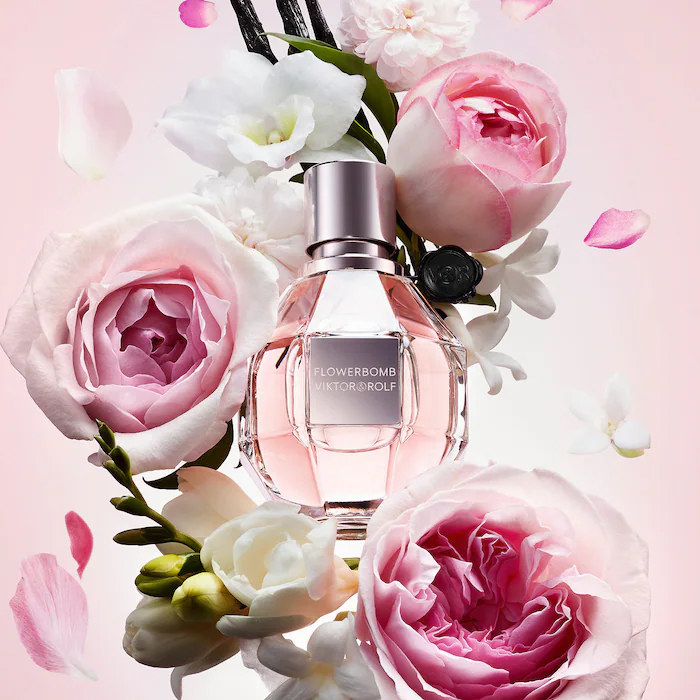 A bottle of perfume surrounded by blooming flowers