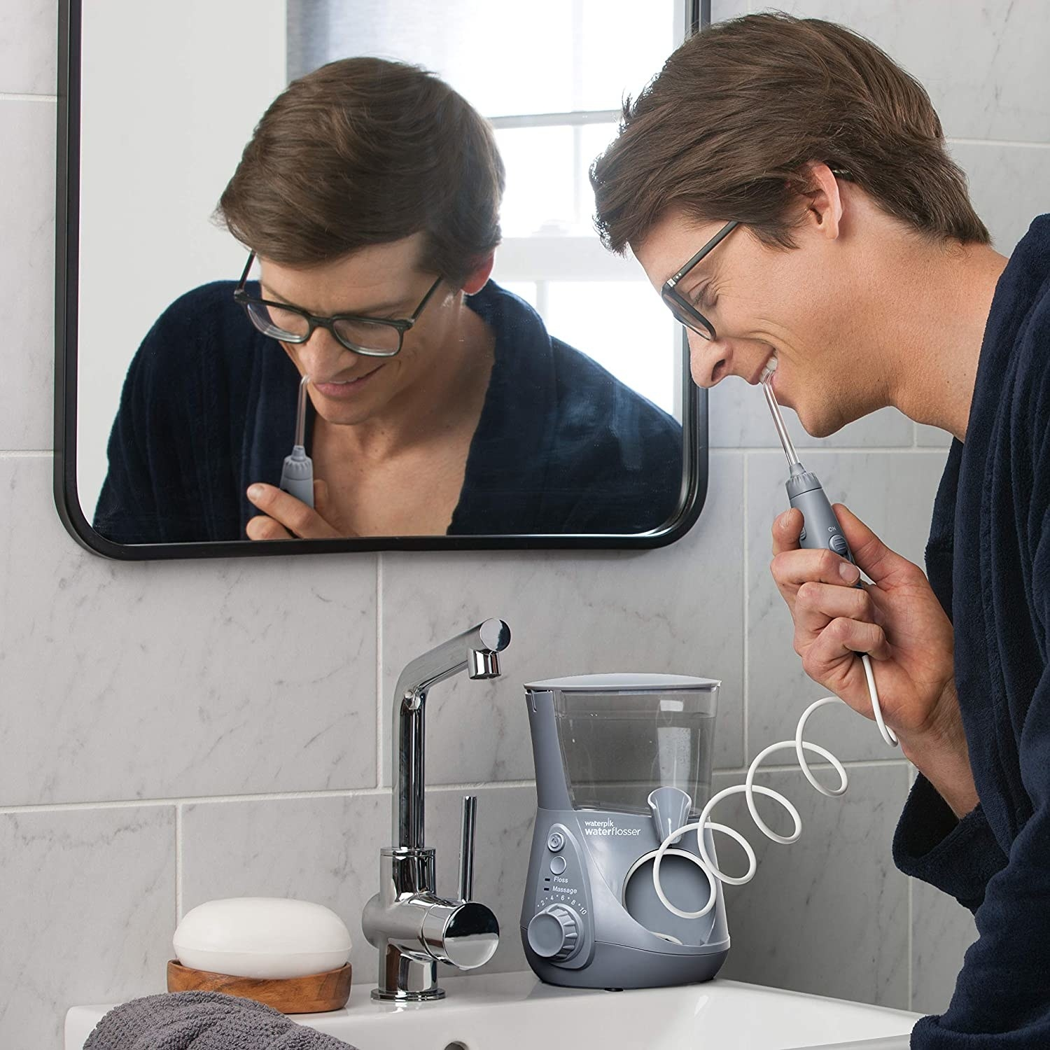 A person cleaning their teeth with a water flosser machine in their bathroom